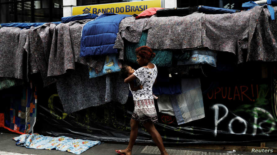 A woman, member of Brazil's Movimento dos Sem-Teto walks next to a set up camp on Paulista Avenue, during a protest to demand affordable low-income housing from the government, in front of the Office of the Presidency of the Republic in Sao Paulo, Br