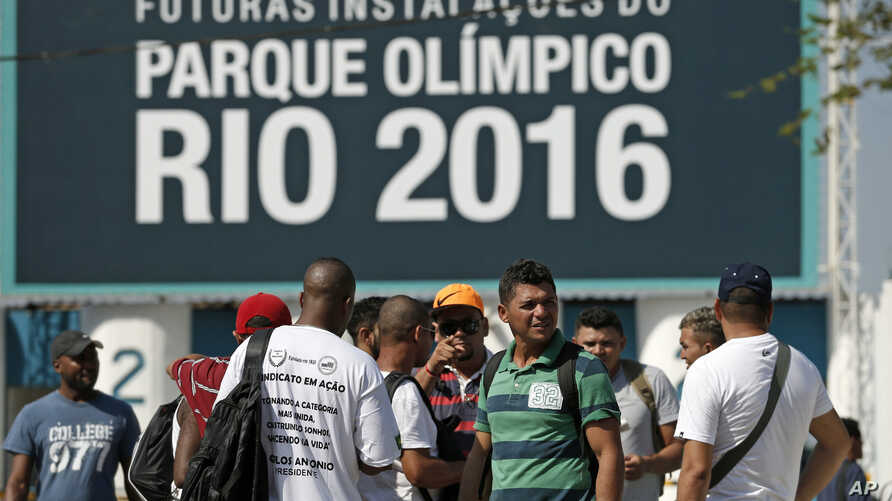 Striking workers stand in front the entrance of the Olympic Park, the main cluster of venues under construction for the 2016 Summer Olympic Games, in Rio de Janeiro, April 8, 2014.
