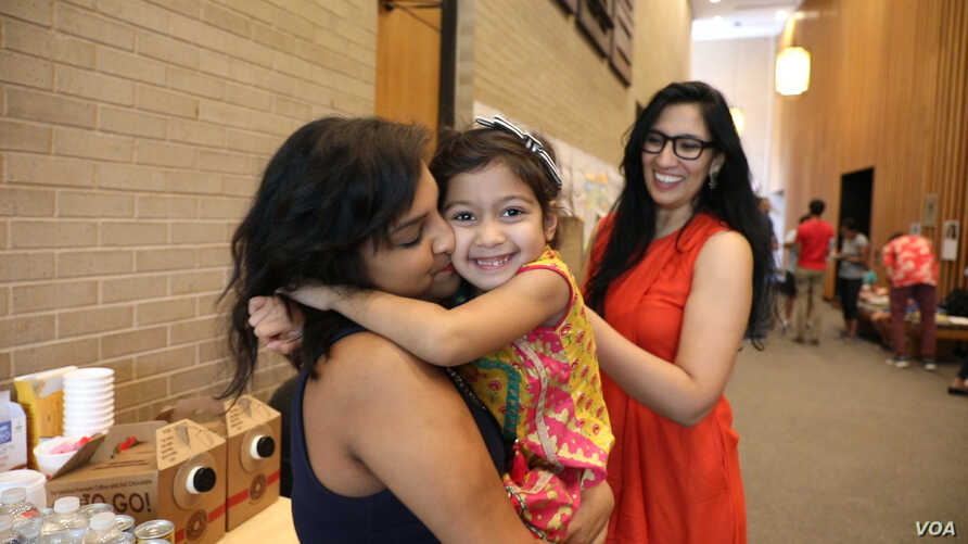"Gayatri ""Genny"" Joshi greets the daughter of her fellow SAYHU co-founder at the summer institute, (E. Sarai/VOA)"