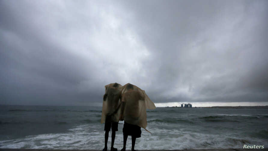 Two men use a plastic sheet to protect themselves from heavy monsoon rain as they stand by the sea in Colombo, Sri Lanka