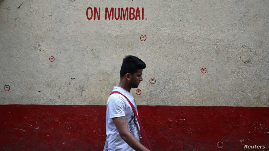 A man walks past a wall riddled with bullet holes opposite to the Nariman House, one of the targets of the November 26, 2008 attacks, after the renaming ceremony of Nariman House as Nariman Light House in Mumbai, India, November 25, 2018.