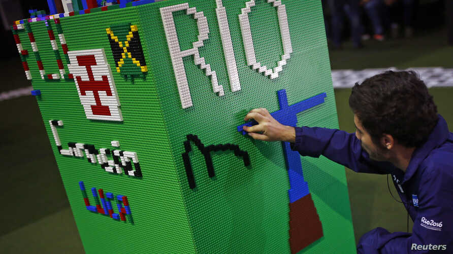 A man arranges LEGO bricks to build a Rio sign during a LEGO presentation of a massive model of the city including the Olympic sites at the Media Center in Rio de Janeiro, Brazil, Aug. 1, 2016.