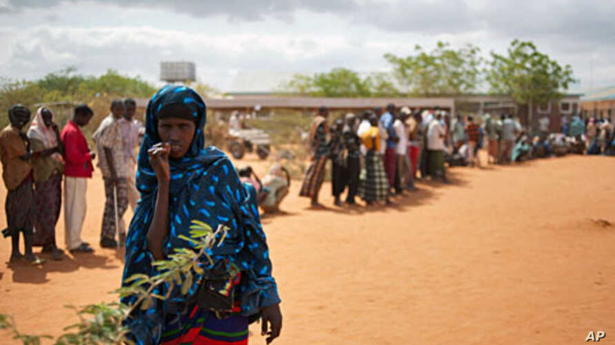 A Somali woman stands in front of Somalis queuing outside the reception center in Ifo refugee camp, one of three camps in Kenya's Dadaab refugee complex on July 25, 2011