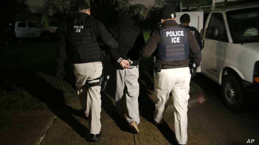 FILE - U.S. Immigration and Customs Enforcement agents escort a handcuffed undocumented immigrant convicted of a felony that was taken into custody during an early morning operation in Dallas.