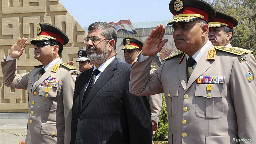 Egypt's President Mohamed Morsi (C) stands after laying a wreath during his visit to the tomb of former President Anwar al-Sadat and the Tomb of the Unknown Soldier during the commemoration of Sinai Liberation Day in Cairo, Apr. 24, 2013.