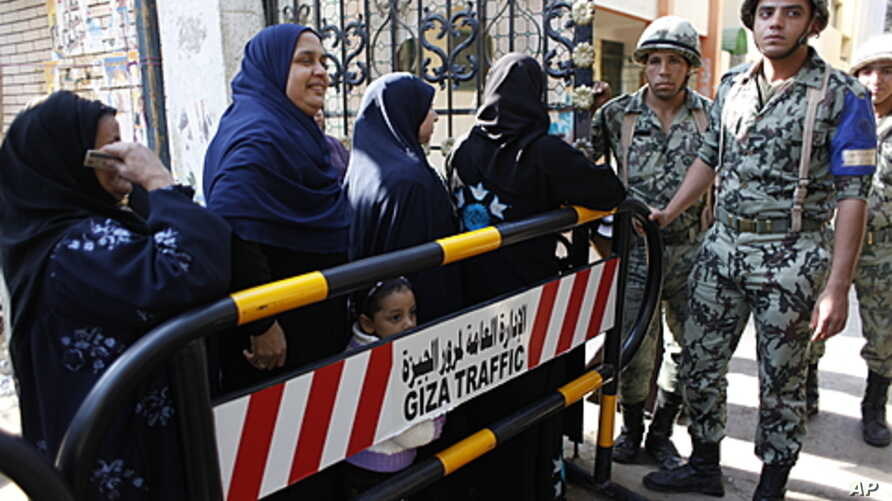 Egyptian women stand in line waiting to cast their votes at the entrance of an election center in Cairo, Egypt, December 15, 2011.