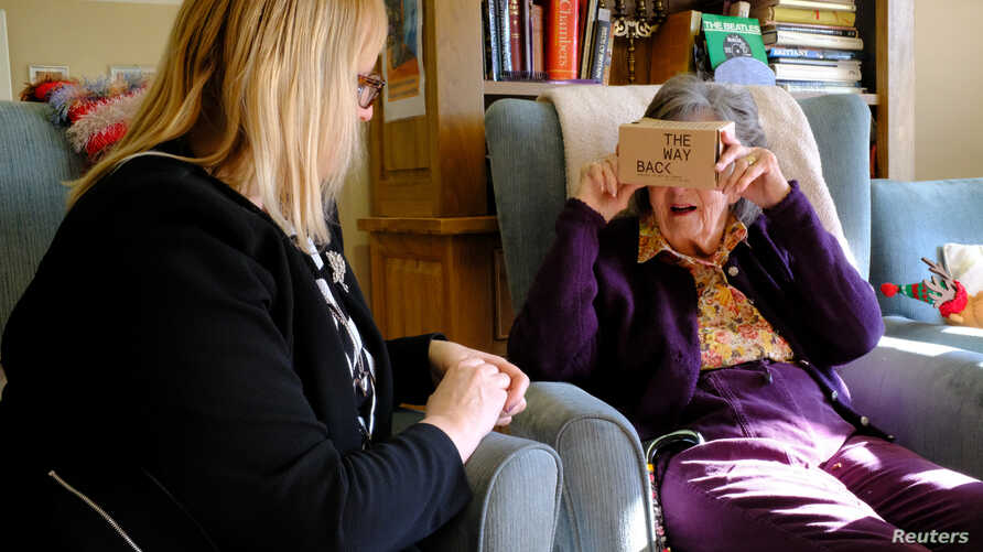FILE - Daphne Padfield, 93, tries out a specialist virtual reality headset at the Langham Court Dementia Home in Hindhead, Britain Feb. 6, 2018.