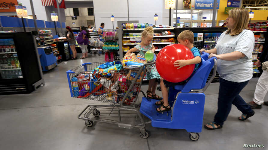 FILE - A family shops at a Wal-Mart Supercenter store in Springdale, Arkansas, June 4, 2015.