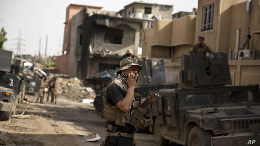 An Iraqi special forces soldier speaks on the radio as troops move from the Yarmouk neighborhood to take another district from Islamic State militant control in Mosul, Iraq, April 12, 2017.