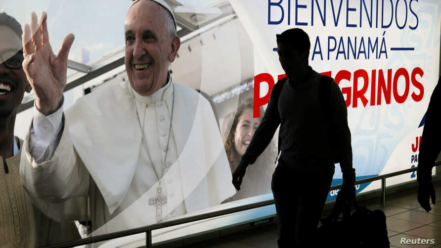 A passenger walks past a poster of Pope Francis at the Tocumen International Airport ahead of Pope Francis' visit for World Youth Day, in Panama City, Panama, Jan. 21, 2019.