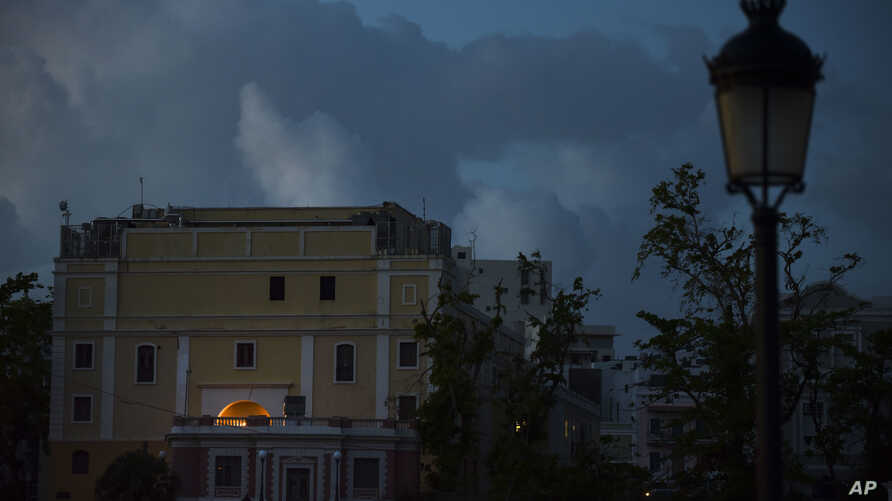 FILE - The streets of Old San Juan are dark after sunset one month after Hurricane Maria in San Juan, Puerto Rico, Oct. 20, 2017.