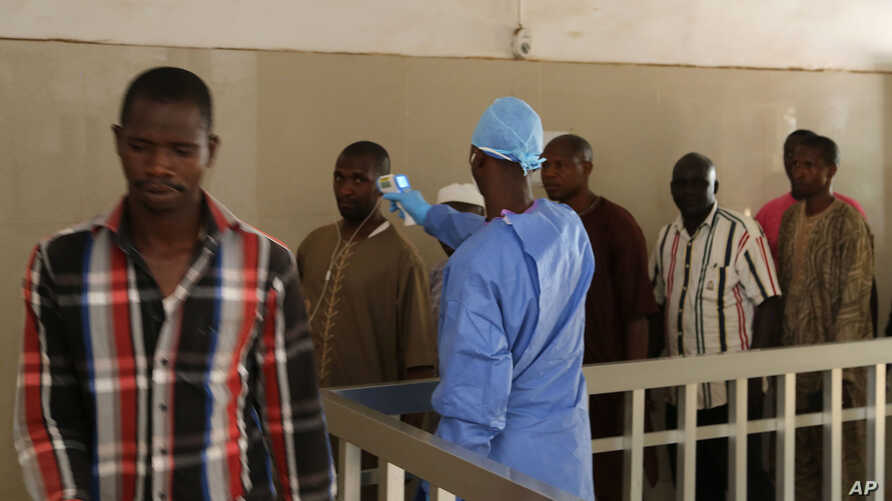 A health worker, center, takes the temperature of people to see if they might be infected by the Ebola virus inside the Ignace Deen government hospital in Conakry, Guinea, March 18, 2016.
