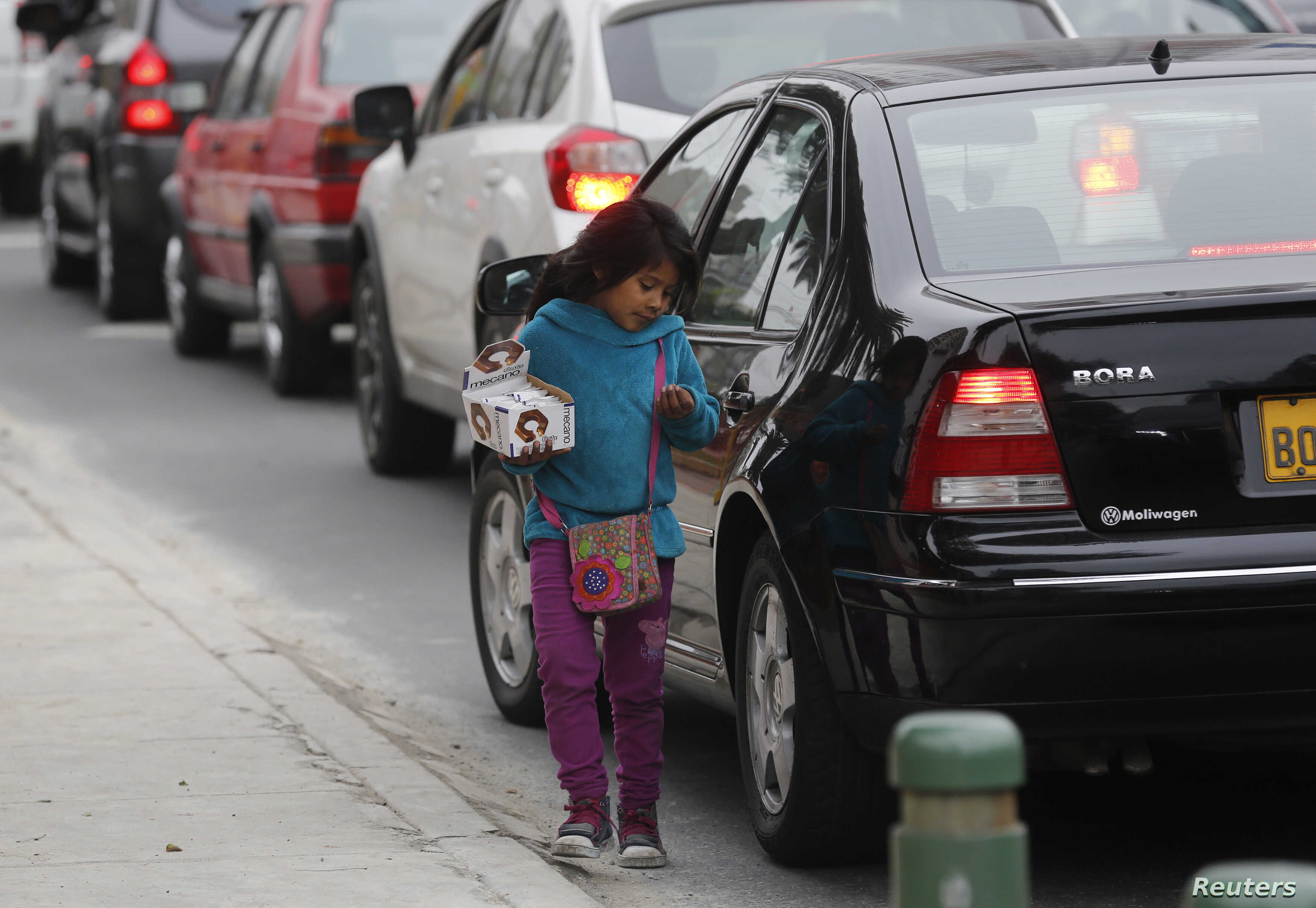 FILE - A girl sells candies along a street in the Miraflores district in Lima, Aug. 8, 2014.