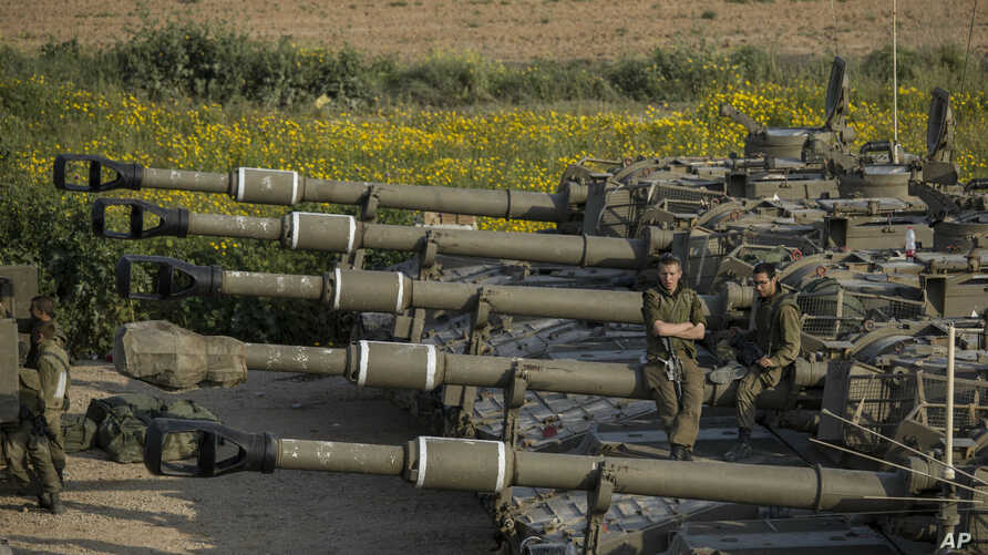 Israeli soldiers sit on top of mobile artillery near the border with Gaza, in southern Israel, March 27, 2019.