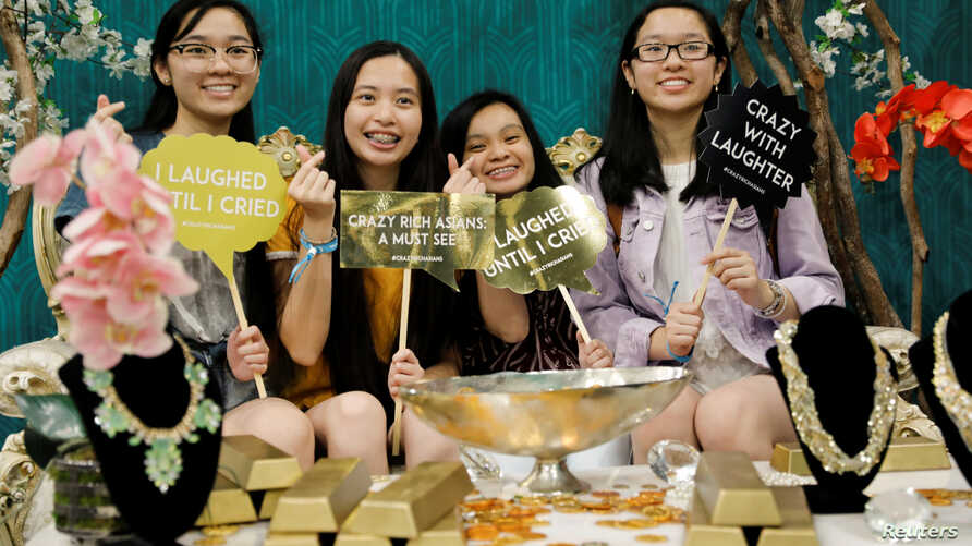 """Attendees at a booth promoting the new movie """"Crazy Rich Asians"""" as they participate at KCON USA, billed as the world's largest Korean culture convention and music festival, in Los Angeles, California, August 10, 2018."""