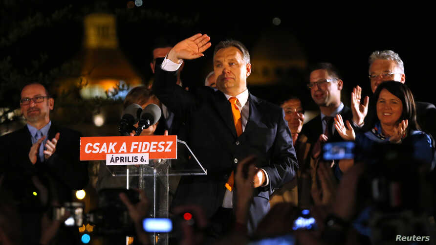 Hungary's Prime Minister Viktor Orban waves to supporters after partial results of parliamentary elections are announced in Budapest April 6, 2014.