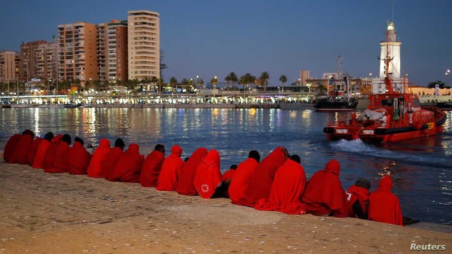 Migrants, part of a group intercepted aboard a dinghy off the coast in the Mediterranean Sea, rest after arriving on a rescue boat at the Port of Malaga, Spain, Dec. 7, 2017.