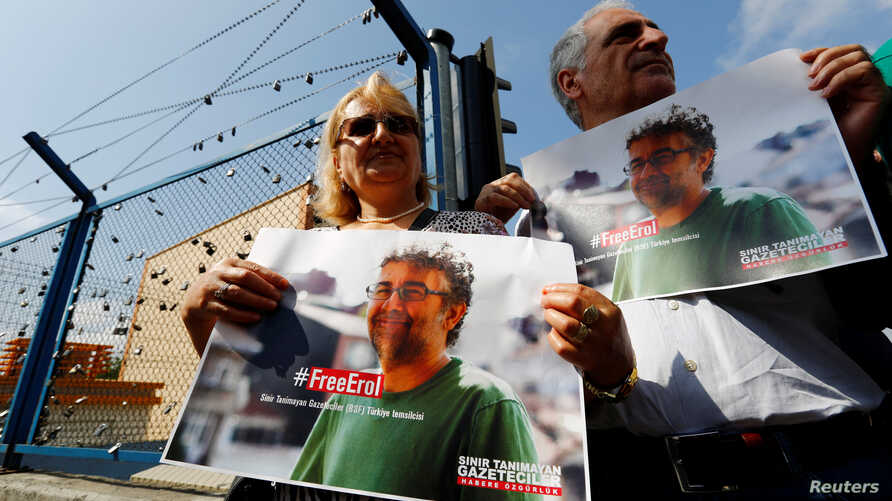 FILE - Demonstrators hold banners with the picture of Erol Onderoglu, local representative of Reporters Without Borders, during a protest against the arrest of three prominent activists for press freedom, in front of Metris prison in Istanbul, Turkey