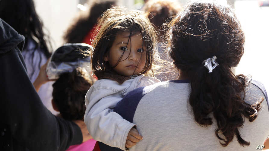 Immigrant families walk to a respite center after they were processed and released by U.S. Customs and Border Protection, June 27, 2018, in McAllen, Texas.