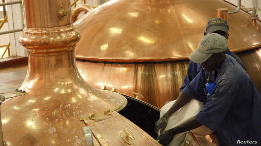 FILE - Workers pour brewing ingredients in a copper kettle at the Nile Brewery Company, east of Uganda's capital Kampala.