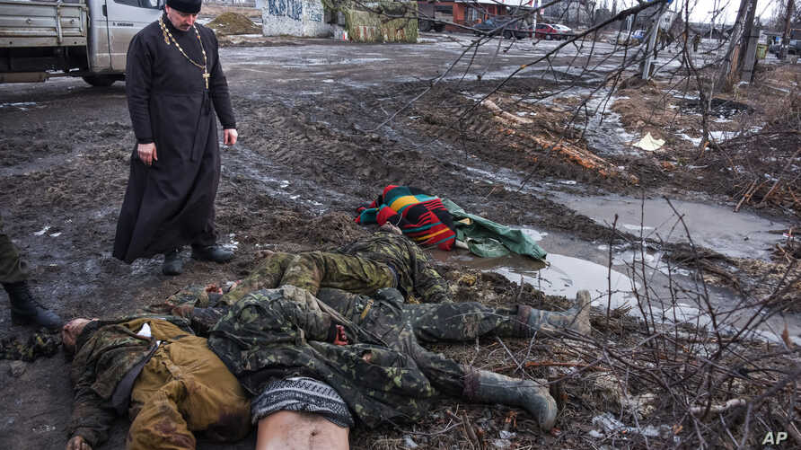 FILE - An Orthodox priest stands next to the bodies of killed Ukrainian soldiers on a checkpoint captured by pro-Russian rebels at the eastern Ukraine town of Krasniy Partizan, Jan. 24, 2015. Fighting has tapered off but continues despite several cea
