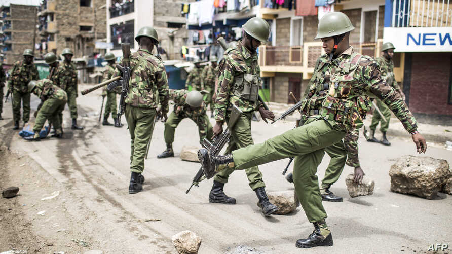 Kenyan police officers clear debris and stones from a barricaded road after a protest by supporters of the National Super Alliance (NASA) opposition coalition presidential candidate at Mathare slum in Nairobi.