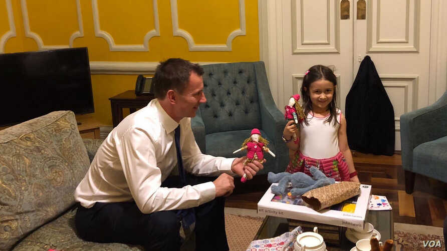 British Foreign Secretary Jeremy Hunt shares a moment with the daughter of jailed Nazanin Zaghari-Ratcliffe, Gabriella, in a photo shared on Twitter by @FreeNazanin.