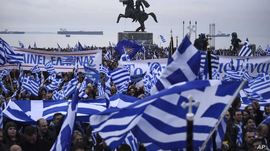 """Greek protesters wave flags and banners during a rally against the use of the term """"Macedonia"""" for the northern neighbouring country's name, at the northern Greek city of Thessaloniki on Sunday, Jan. 21, 2018."""