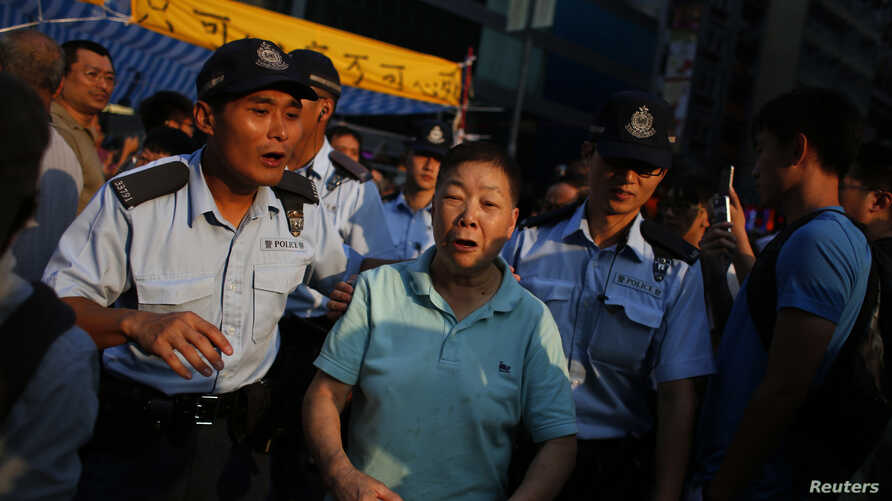 Police escort an anti-Occupy Central supporter to leave an area to prevent a confrontation with pro-democracy protesters inside a tent, which is block a main road at Hong Kong's Mongkok shopping district, Oct. 8, 2014.