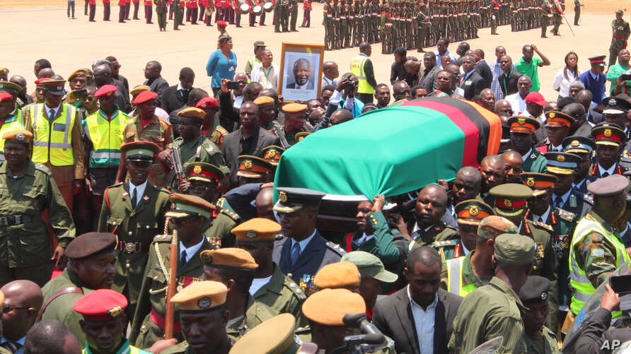Members of the Zambian Defence Forces and other government officials attend a ceremony to welcome the body of former Zambian President Michael Sata  at Kenneth Kaunda International Airport in Lusaka, Nov.1, 2014.