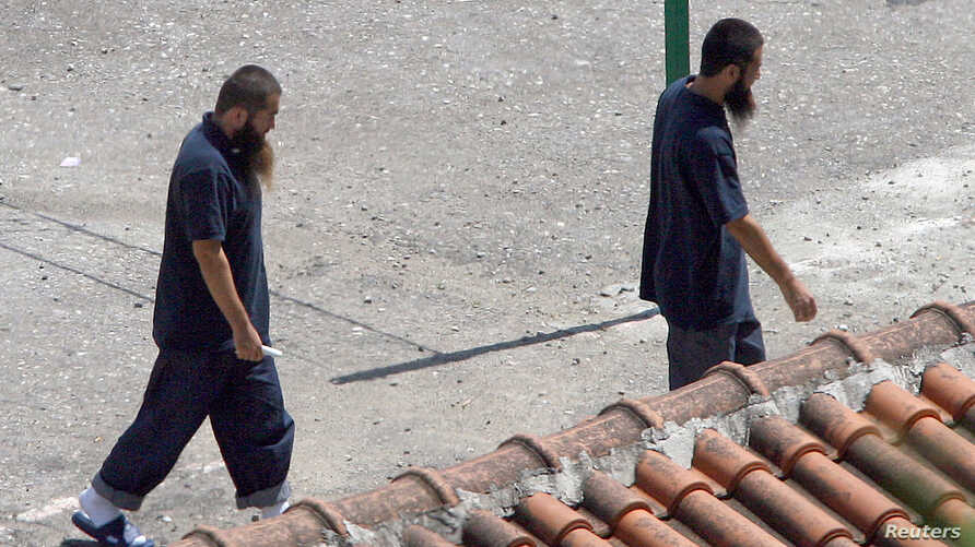 FILE - Two Chinese Uighurs, released from Guantanamo in 2006, are seen following their arrival at a resettlement center in Tirana, Albania.
