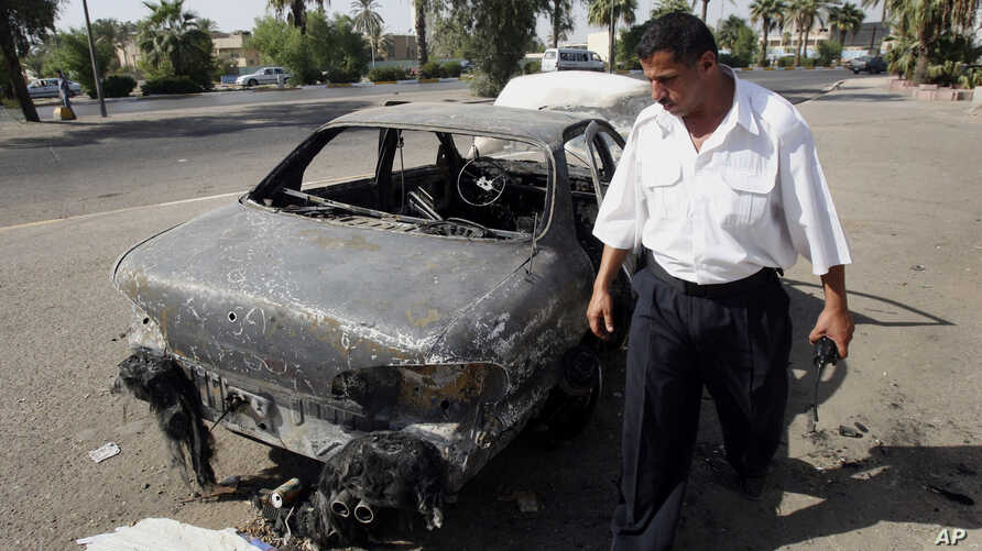FILE - An Iraqi traffic policeman inspecting a car destroyed by a Blackwater security detail in al-Nisoor Square in Baghdad, Iraq, Sept. 25, 2007.
