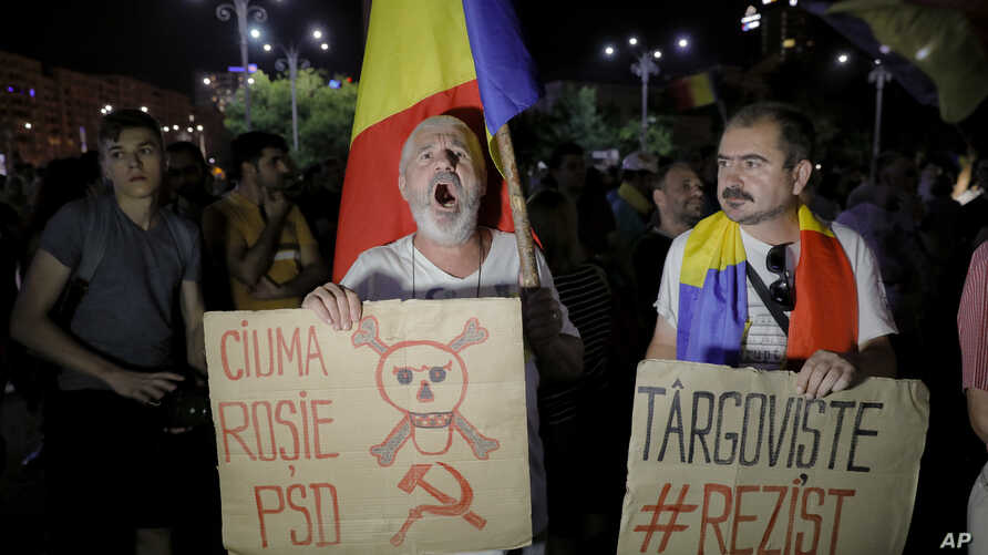 """Protesters shout anti-government slogans holding a banner that reads """"PSD (Social Democratic Party) - The red plague"""" outside the government headquarters in Bucharest, Romania, Sunday, Aug. 27, 2017."""