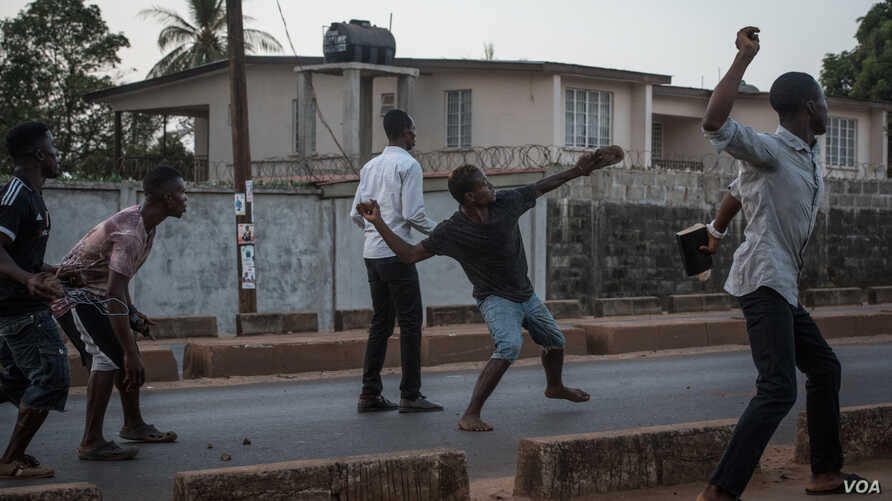 Supporters of the opposition Sierra Leone People's Party throw rocks at police following an alleged incident at party headquarters in Freetown'S Goderich neighborhood, March 7, 2018. (J. Patinkin/VOA)