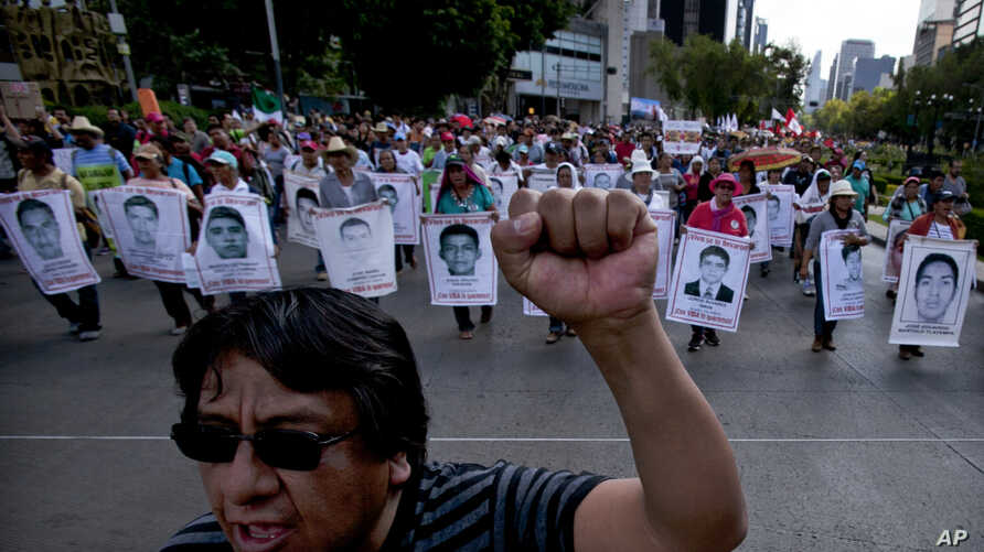 Relatives of the 43 missing students from the Isidro Burgos rural teachers college march holding pictures of their missing loved ones during a protest in Mexico City, July 26, 2015.