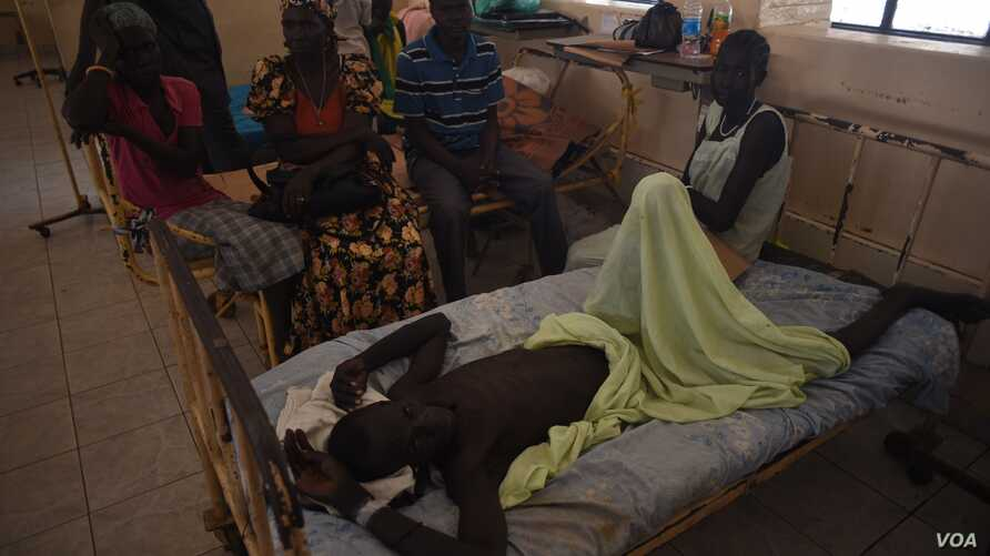 A man who has waited for surgery for a week lies with his family around him at Juba Teaching Hospital, South Sudan's largest medical facility, May 23, 2016. (J. Patinkin/VOA)