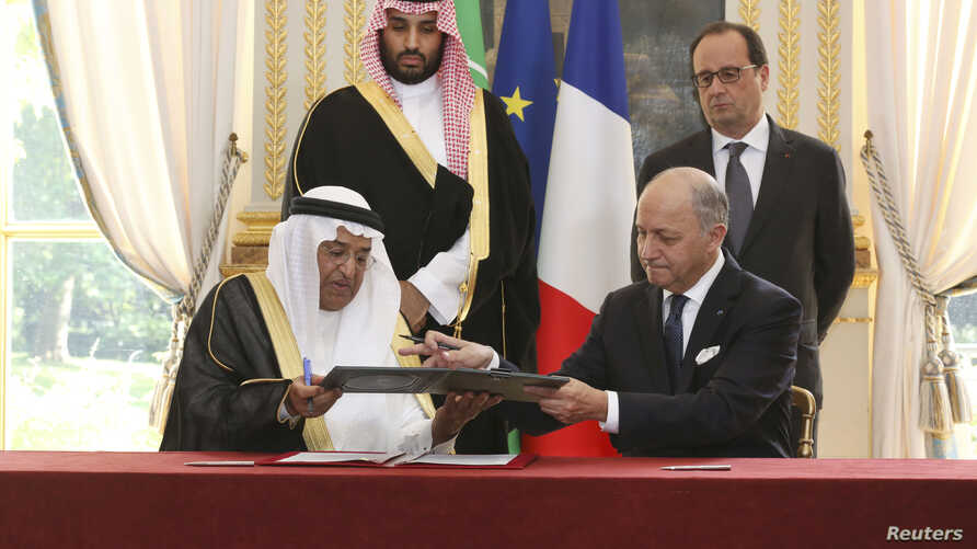 French Foreign Minister Laurent Fabius (R), exchanges documents with Dr. Hashim Yamani, the President of King Abdullah City for Atomic and Renewable Energy, after signing an agreement between France and Saudi Arabia, in front of French President Fran