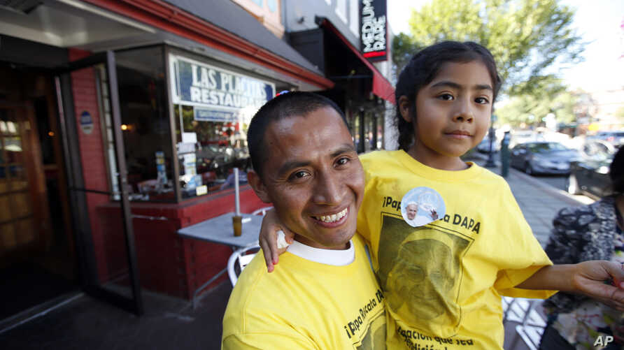 Raul Cruz, from suburban Los Angeles, holds his daughter Sophie Cruz, 5, after an interview with the AP in Washington,, Sept. 23, 2015.