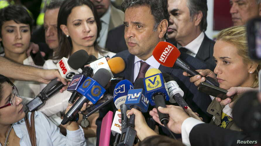 Brazilian Senator Aecio Neves (C) speaks to the media next to Lilian Tintori (R), wife of opposition leader Leopoldo Lopez, Patricia Ceballos (back L), mayor of San Cristobal and wife of jailed former mayor Daniel Ceballos, and opposition leader Mari