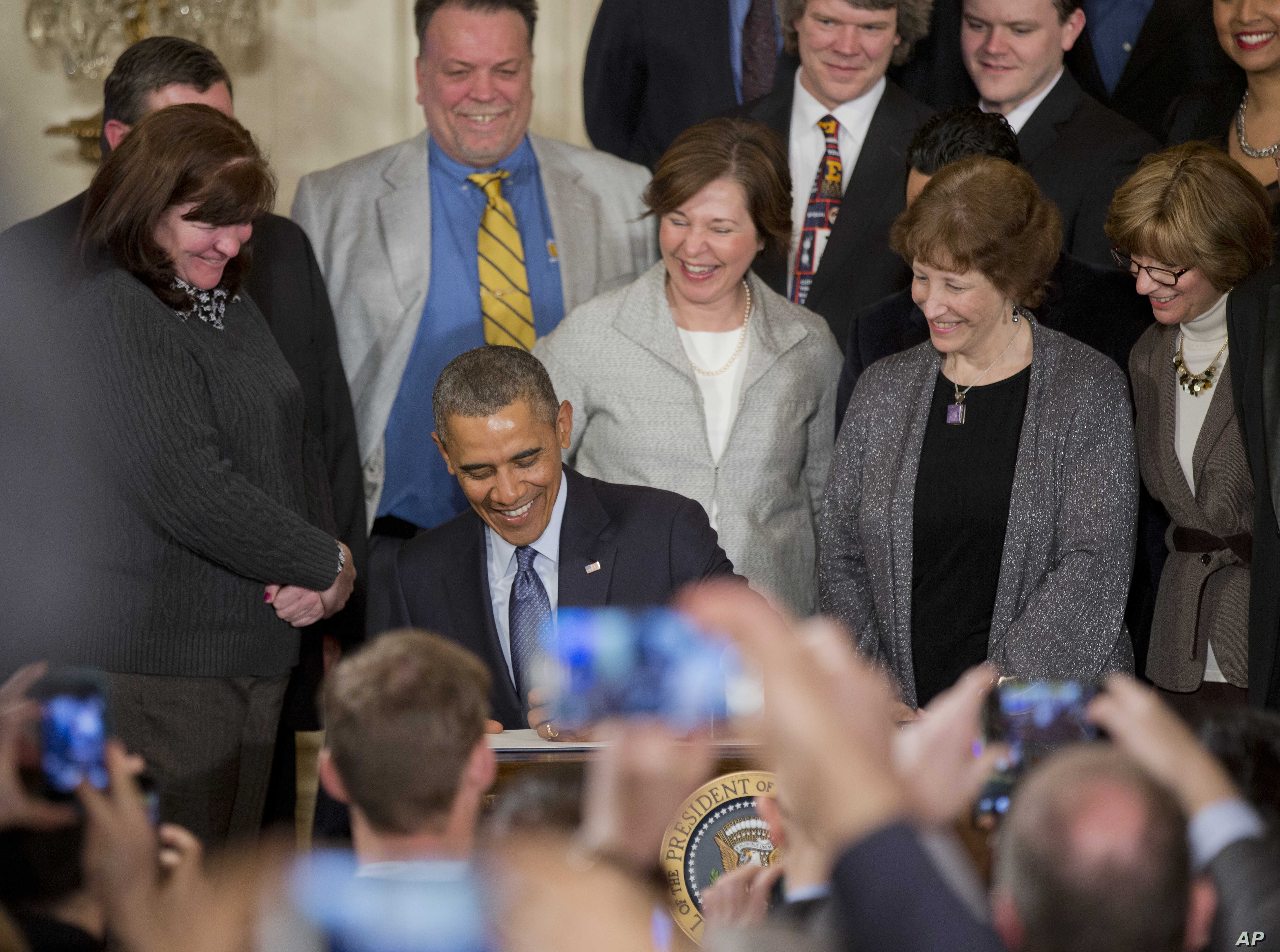 President Barack Obama signs a Presidential Memorandum to modernize overtime protections, in the East Room of the White House in Washington, Mar. 13, 2014.