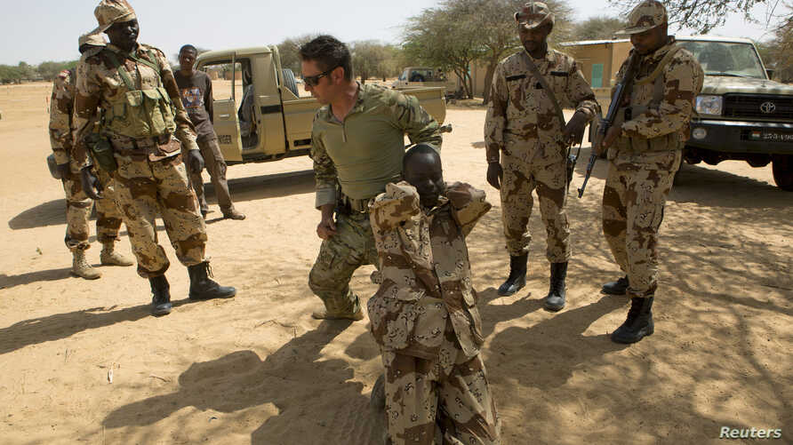 FILE - A U.S. special forces soldier demonstrates how to detain a suspect during Flintlock 2014, a U.S.-led international training mission for African militaries, in Diffa, March 4, 2014.