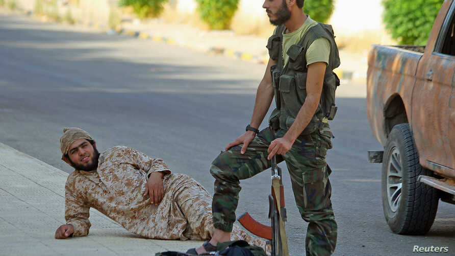 """Fighters from a coalition of rebel groups called """"Jaish al Fateh"""" rest with their weapons in the Hama countryside, Syria, July 29, 2015."""