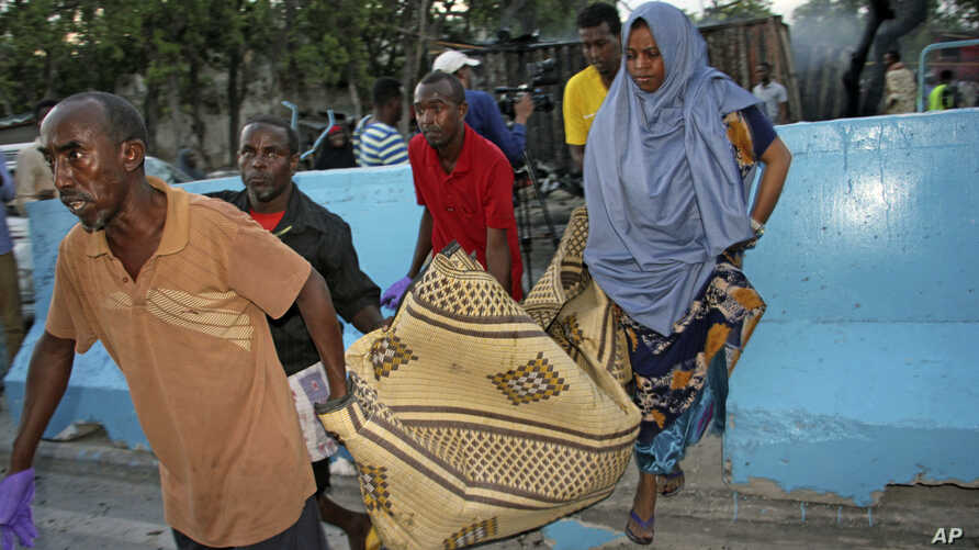 Somalis carry away the dead body of a person who was killed when a car bomb detonated in Mogadishu, Somalia, May 24, 2017.