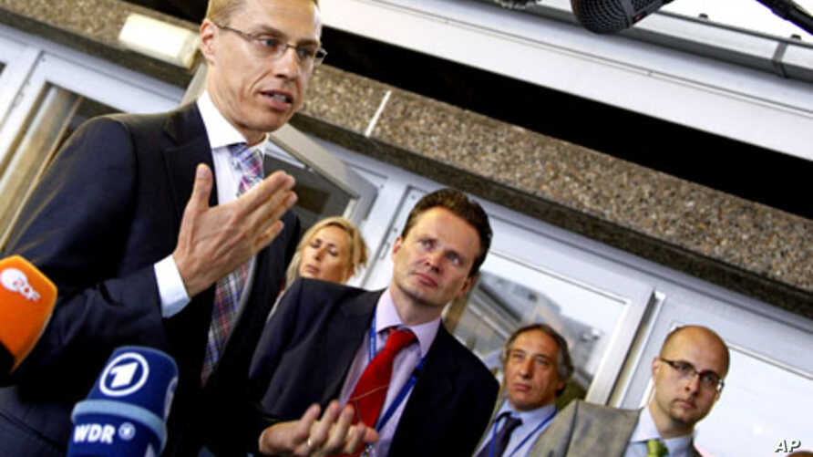 Finland's Foreign Minister Alexander Stubb, left, speaks with journalists as he arrives for a meeting of EU foreign ministers in Luxembourg. EU foreign ministers expanded sanctions against Syria as brutal repression of an uprising in the Middle Easte