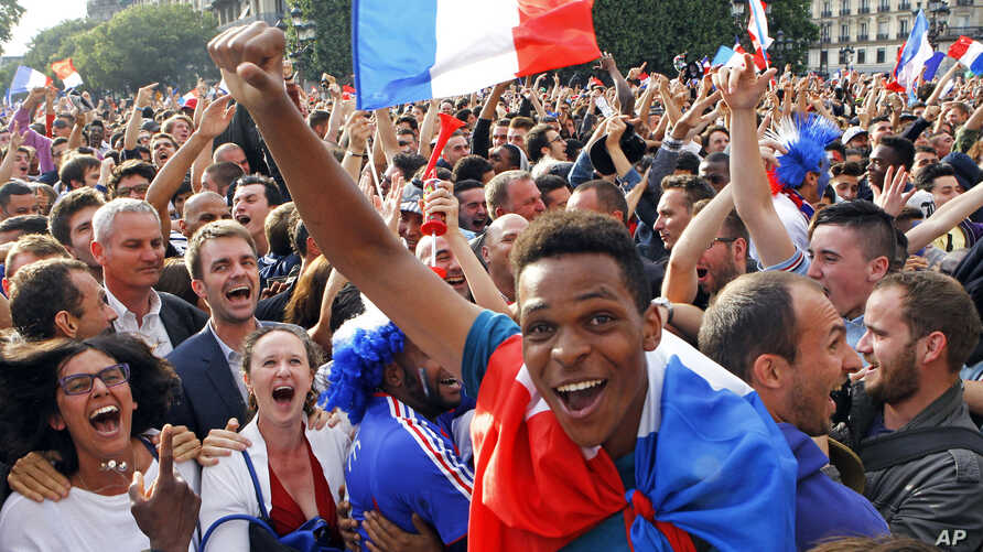 French soccer fans celebrate after France scored the first goal, as they watch the World Cup soccer match between France and Nigeria being shown live on a giant screen, in front of Paris City Hall, June 30, 2014.