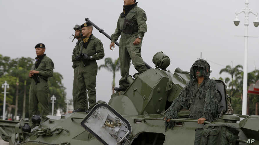 Venezuela CrisisSoldiers stand atop an armored vehicle at the entrance of Fort Tiuna in Caracas, Venezuela, Aug. 26, 2017.