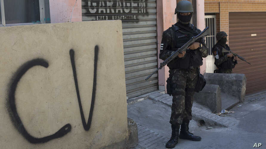 "FILE - A soldier stands guard next to a wall tagged with the acronym ""CV"" identifying the criminal organization ""Comando Vermelho"" or Red Command, during an operation at the Rocinha slum, in Rio de Janeiro, Brazil, Tuesday, Oct. 10, 2017."