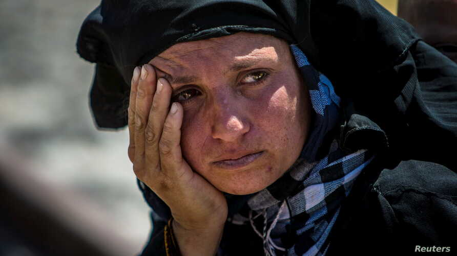 A woman reacts as she rests from walking back to Tel Abyad town, Raqqa governorate, after fleeing Maskana town in the Aleppo countryside June 16, 2015. With a string of victories over Islamic State, Syria's Kurds are proving themselves an ever more d