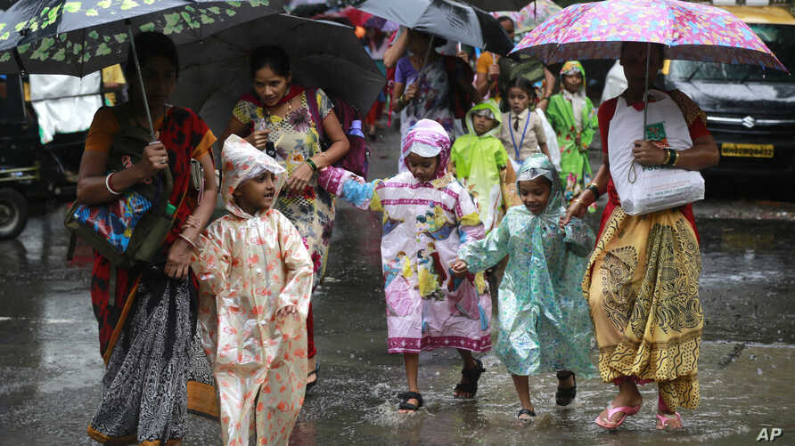 Mothers walk with their children wearing raincoats as they cross a flooded road in Mumbai, India, Tuesday, July 26, 2016.