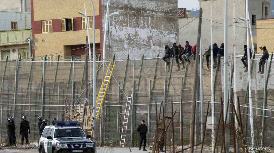 FILE - African migrants are seen sitting atop a border fence as Spanish Civil Guard officers stand below, on the border between Morocco and Spain's north African enclave of Melilla February 10, 2015.